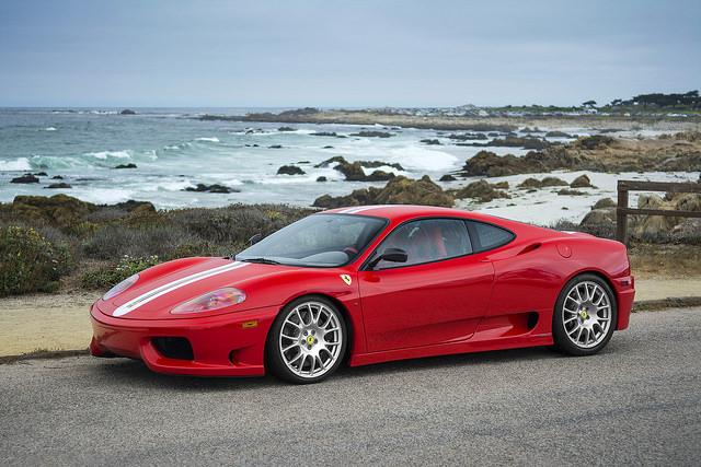 Une Ferrari rouge devant la mer.