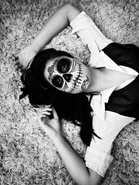 Une femme maquillée pour Halloween, allongée sur un tapis.