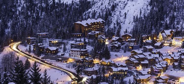 Une station de ski enneigée et ses installations touristiques toutes éclairées.