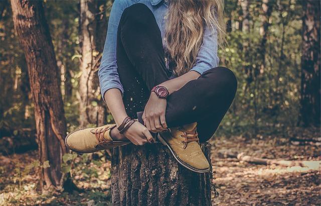 Une femme aux cheveux longs est assise sur un tronc d'arbre, dans la forêt.