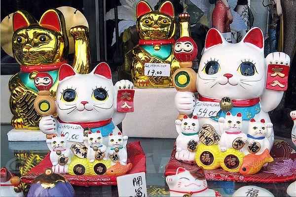Des figurines maneki-neko, porte-bonheurs japonais symbolisés par un chat qui lève une patte, dans une vitrine.
