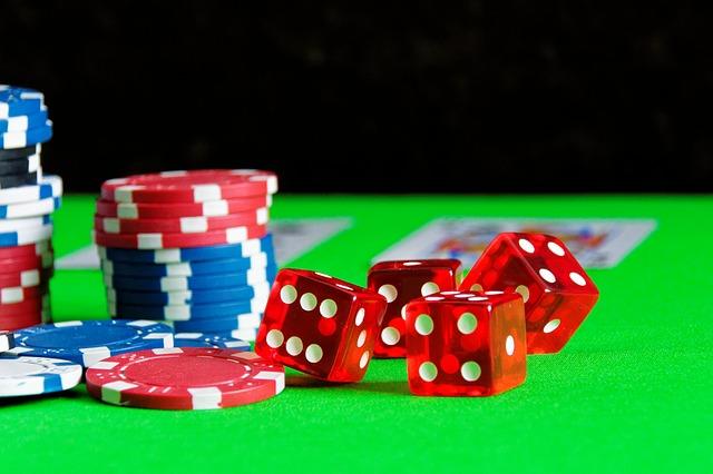 Des dés et des jetons de jeux, sur un tapis de table de casino.