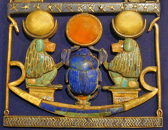 Photographie d'une plaque décorative avec un scarabée central en position solaire.
