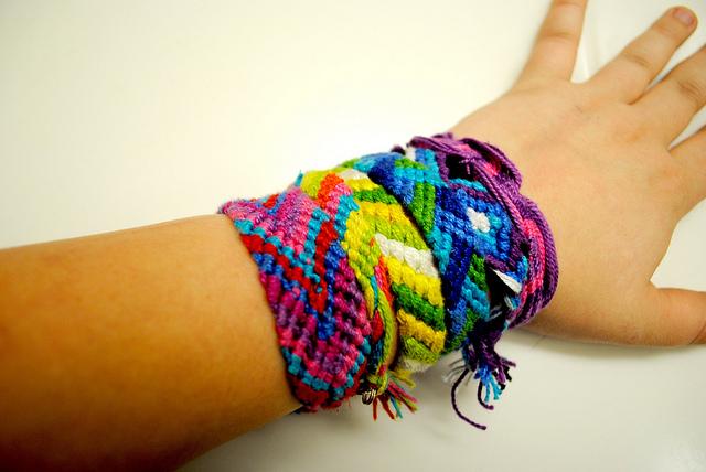 Photographie d'un avant bras couvert de bracelets brésiliens.