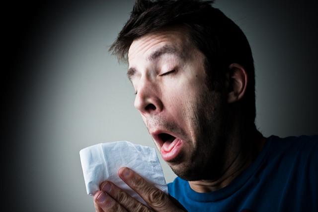 Photographie d'une personne en train d'éternuer dans un mouchoir.