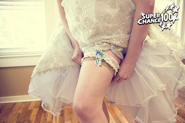 Photographie d'une mariée revêtant une jarretière.