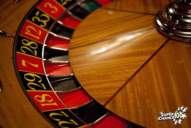Photographie d'une roulette de casino avec des chiffres sur fond rouge et noir.
