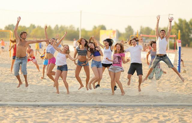 Un groupe d'amis saute en l'air sur la plage.