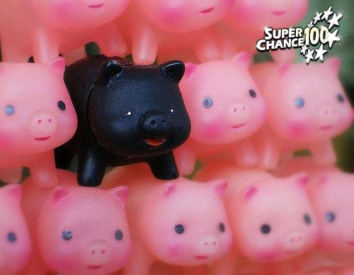 Photographie de figurines de cochon rose superposés avec un cochon noir dans le tas.
