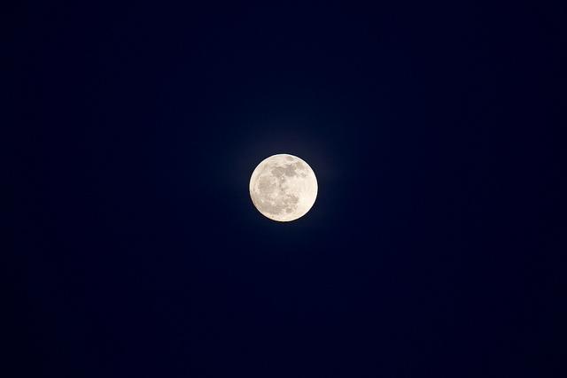 Photographie d'une pleine lune en pleine nuit.