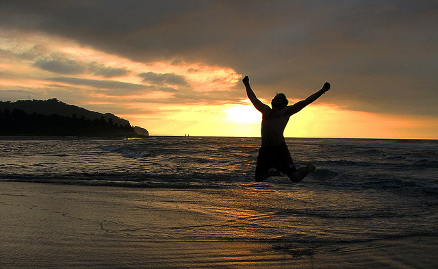 Un homme saute en l'air de joie au bord de la mer.