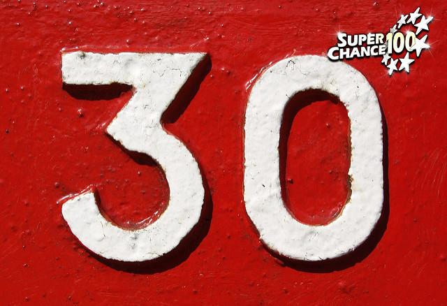 Mur rouge sur lequel est peint en blanc le chiffre 30.