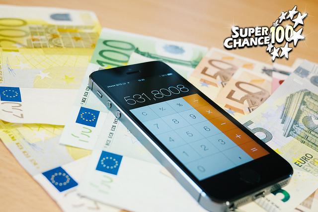 Photographie de plusieurs billets de banque étalés sur la table et d'un smartphone en mode calculatrice.