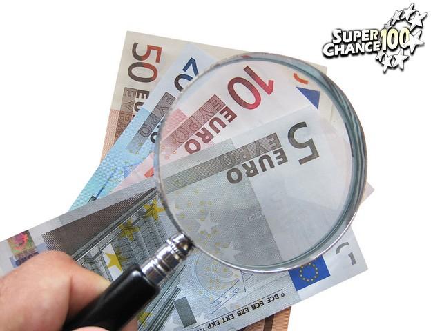 Une loupe sur des billets d'euros.