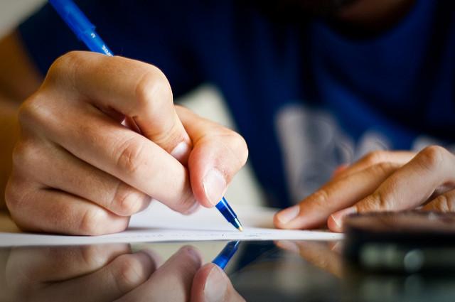 Personne en train d'écrire sur du papier.