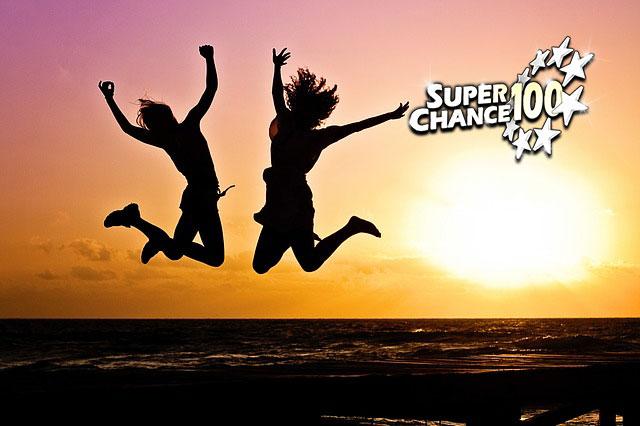 Photographie de deux personnes heureuses sautant devant un coucher de soleil.