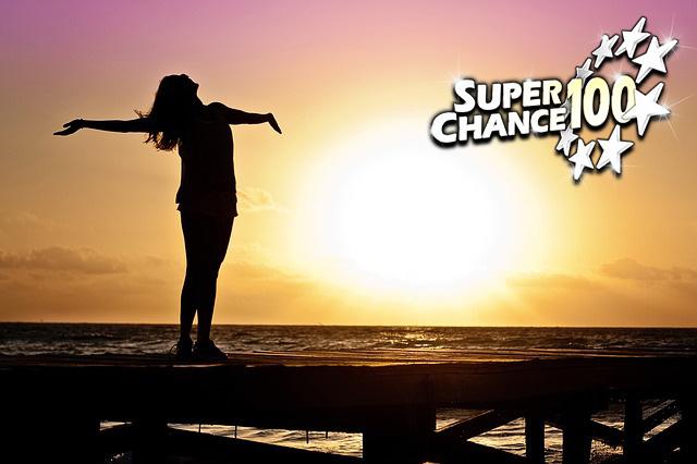 Photographie d'une femme heureuse devant un coucher de soleil.