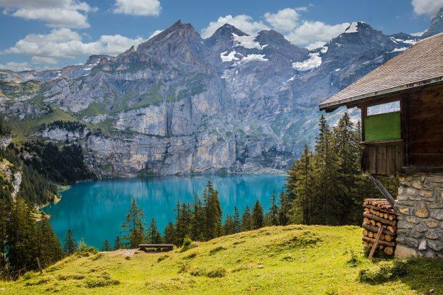 C'est un paysage suisse avec un lac et une petite maison sur la droite , et des montagnes au loin.