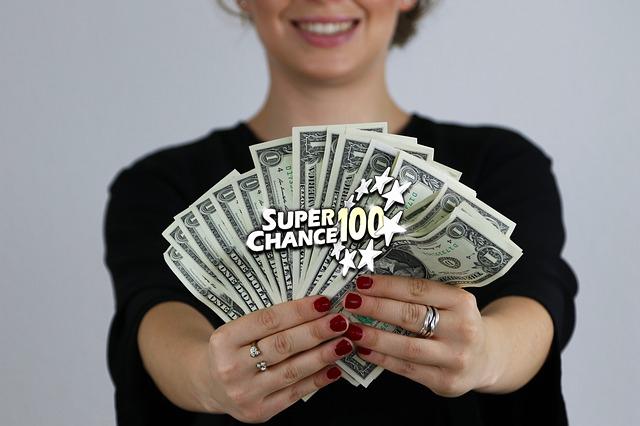 Femme tenant des liasses de billets de banque.