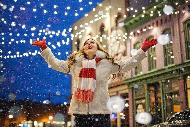 C'est une femme heureuse au milieu de décorations de Noel.